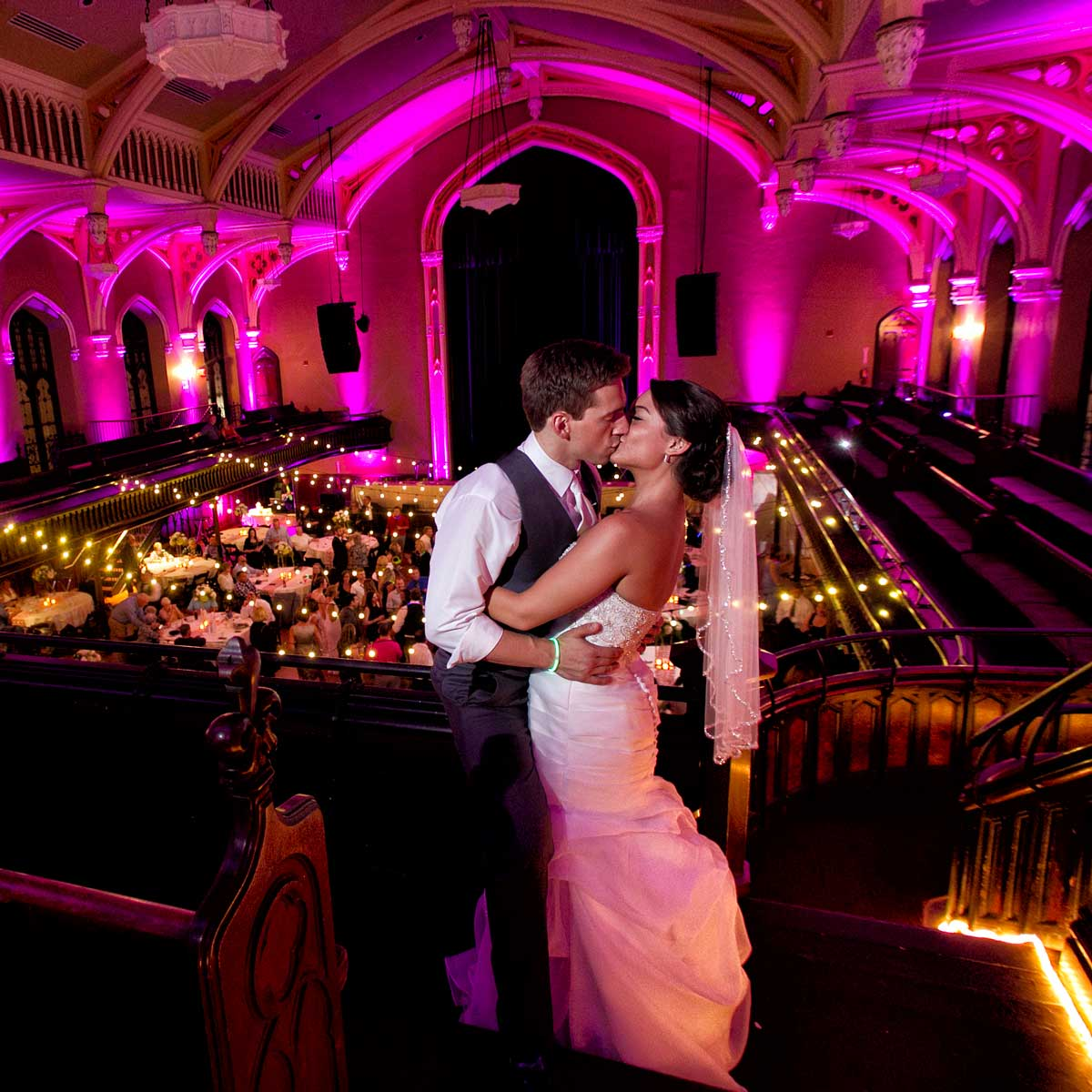 Bride and Groom kiss on the balcony at Statler City with ballroom lit with pink uplighting in the background