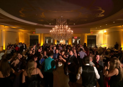 Amber uplighting set off a ballroom that is decorated for a wedding reception