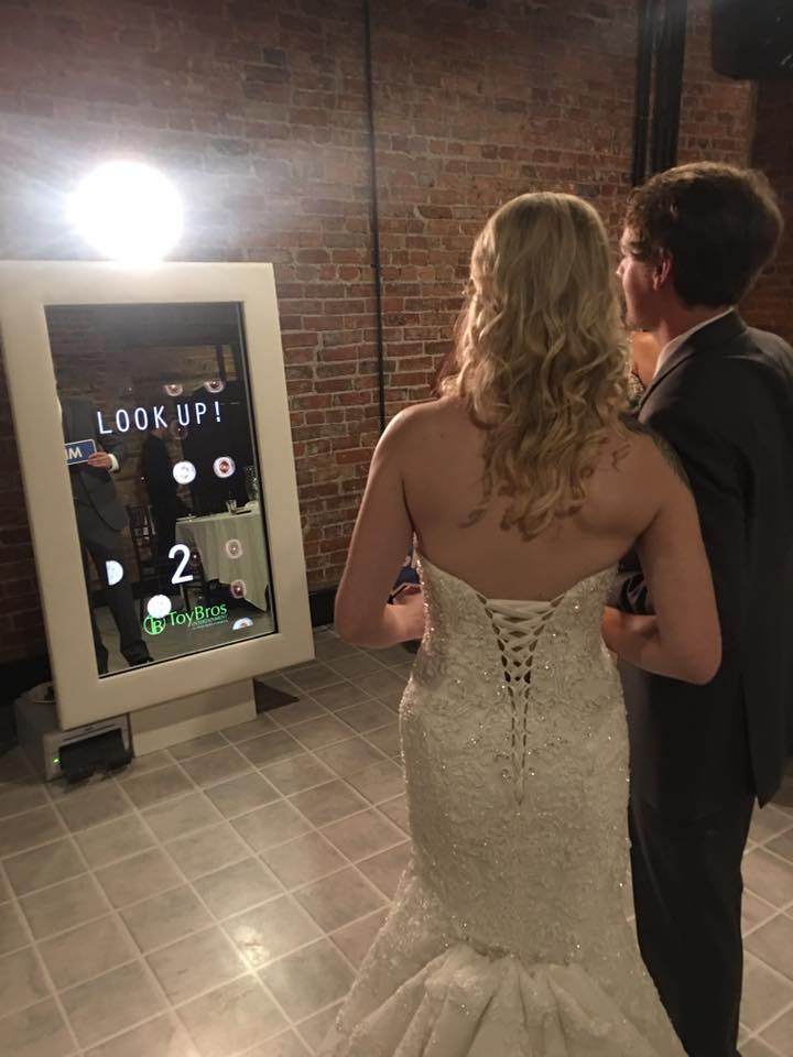 Bride and Groom Posing for Photos in front of the Mirror Booth provided by Toy Bros Entertainment in Buffalo, NY