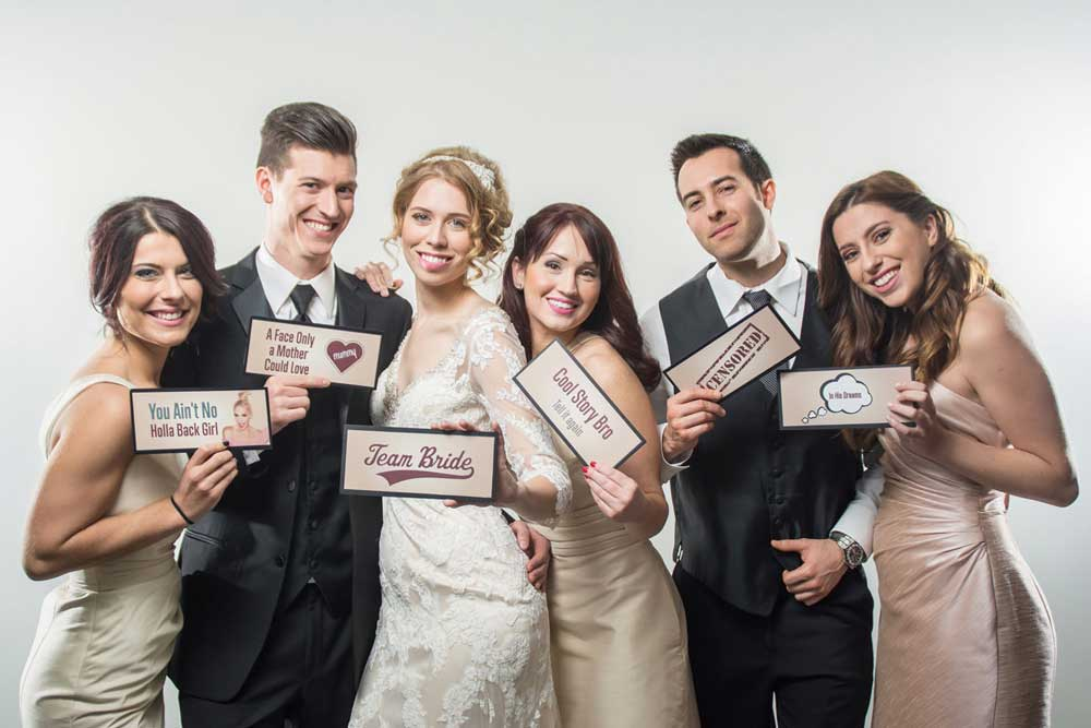 Wedding party poses for a photo with custom photo booth props from Toy Bros Entertainment