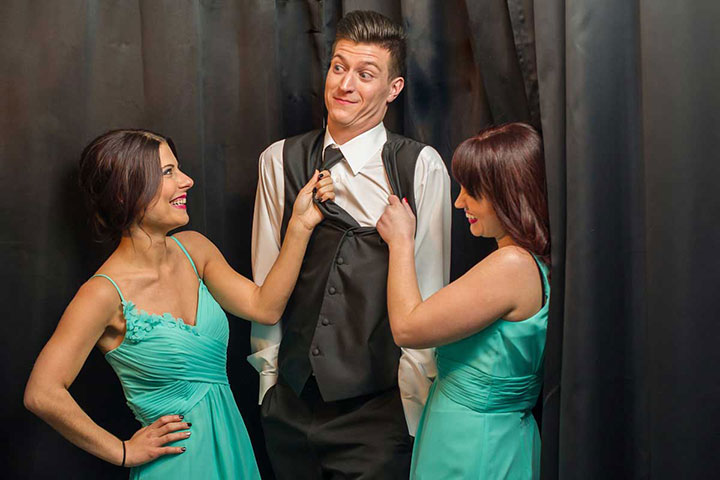 Two Bridesmaids and a Groomsman pose in an Enclosed Photo Booth at a wedding in Buffalo, NY