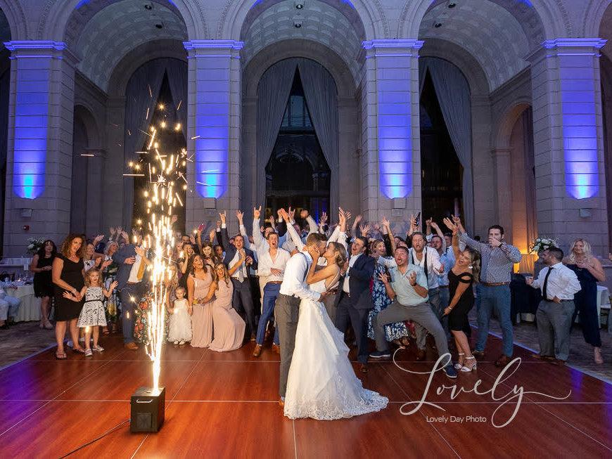 Bride and Groom kissing under indoor fireworks